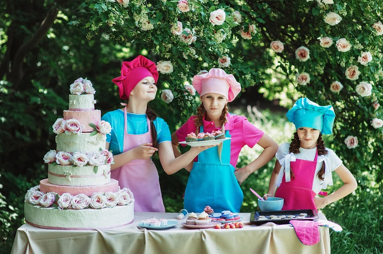three kid chefs hold cakes and cupcakes
