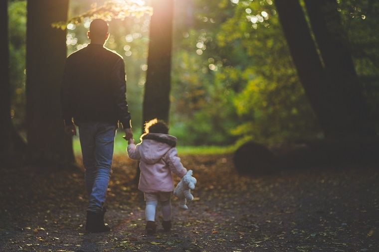 Father walking daughter through woods