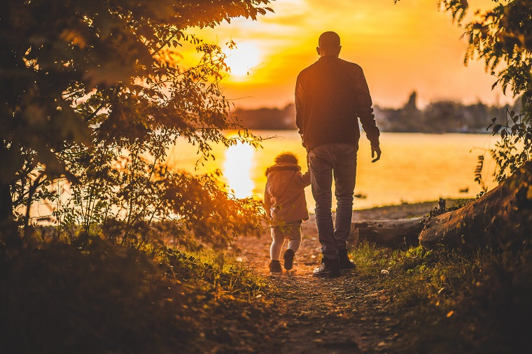 father walking with child at sunset