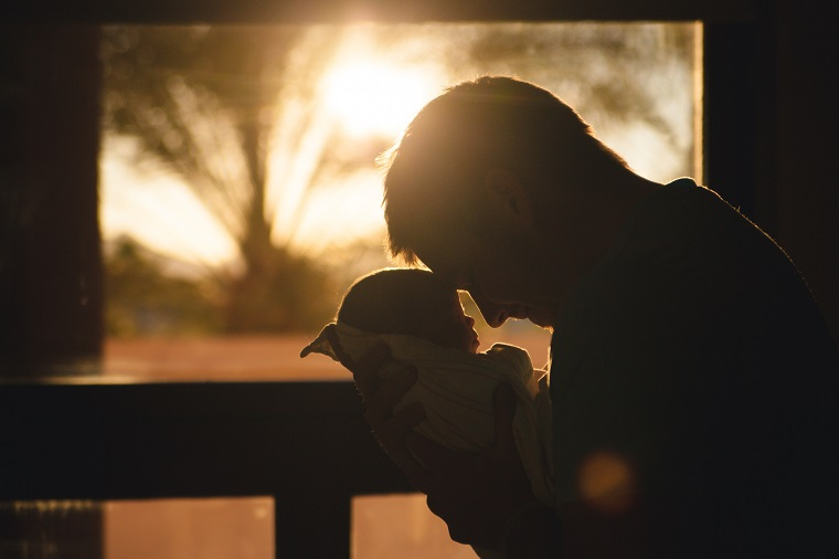 new father holding baby at sunset