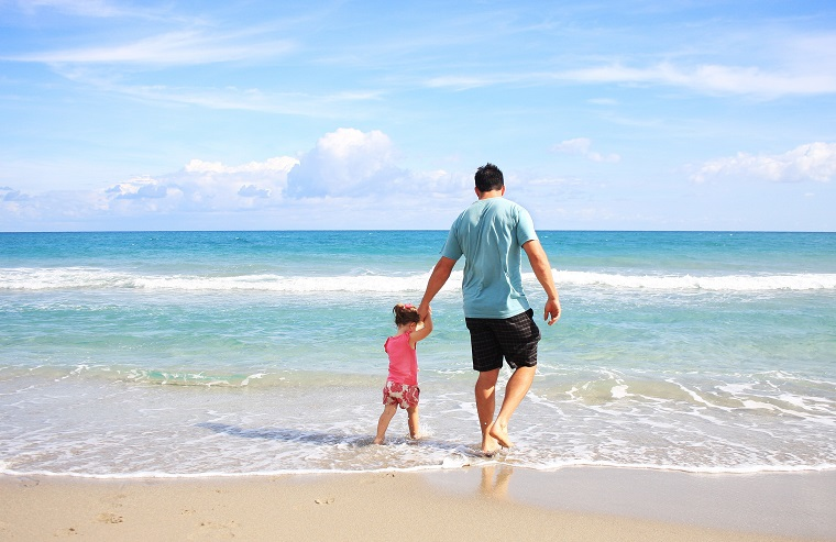 father walks daughter along the beach