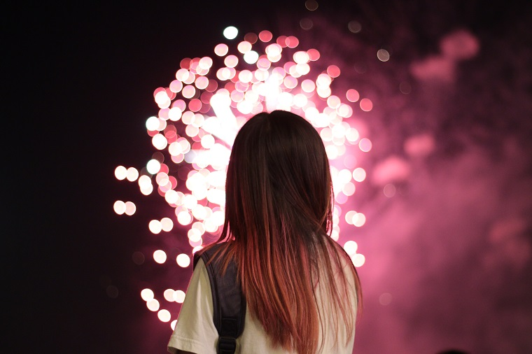 woman with pink hair watching pink fireworks