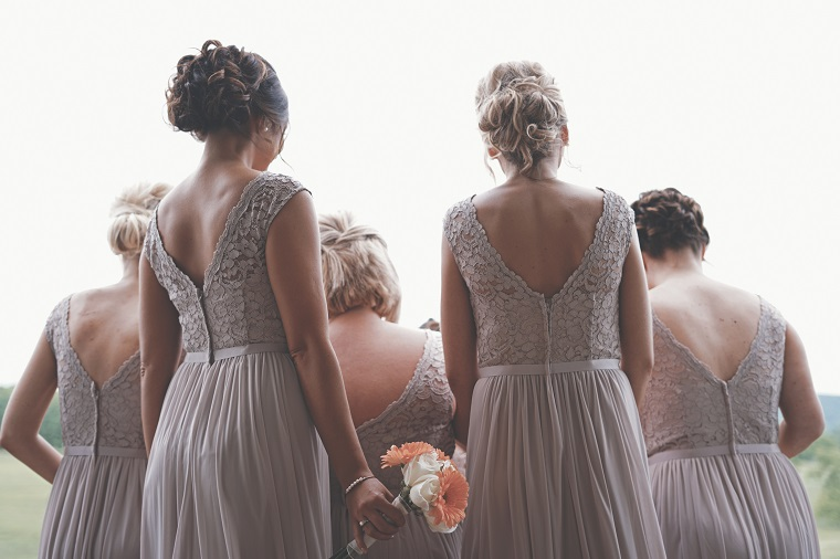 Bridesmaids wearing the same dress looking at the bride