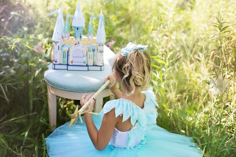 girl dressed as princess plays with castle