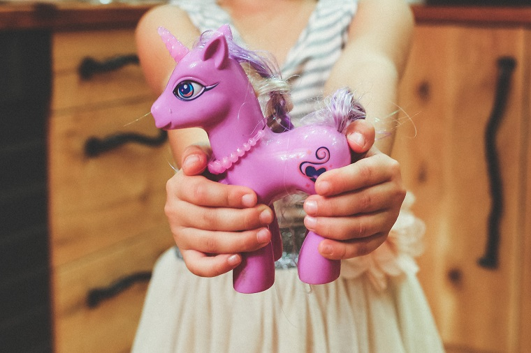 girl holding a unicorn toy