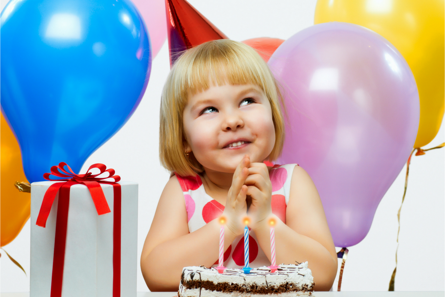 Young birthday girl smiling in front of cake and next to gift at her party