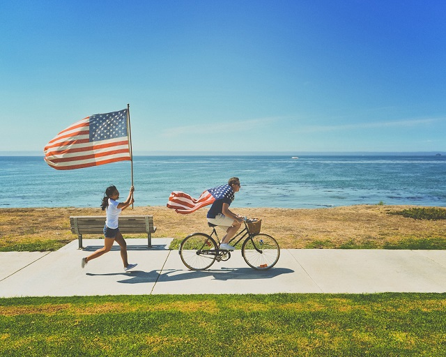 couple carrying the american flag on memorial day