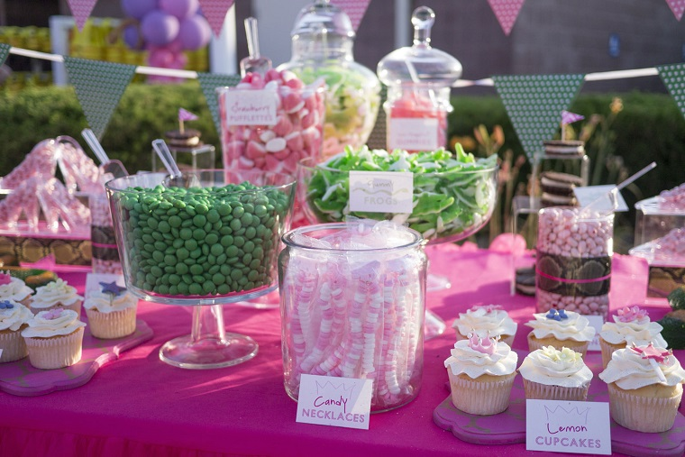 Candy jars and cupcakes on top of pink decorated table at a birthday party