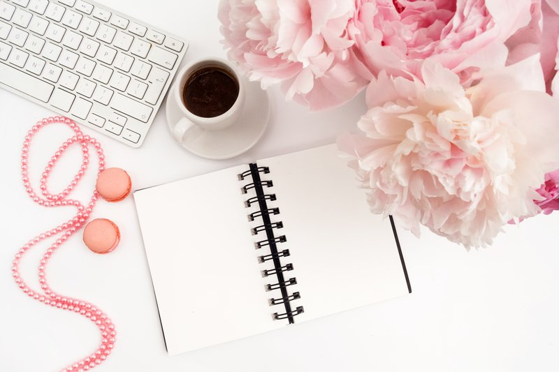 Elegant planning notebook next to a mug of coffee, flowers and a keyboard