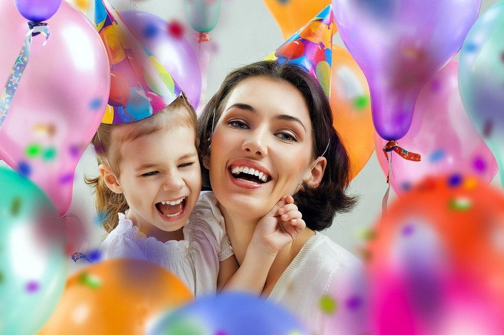 Mom and daughter smiling at a birthday party with balloons