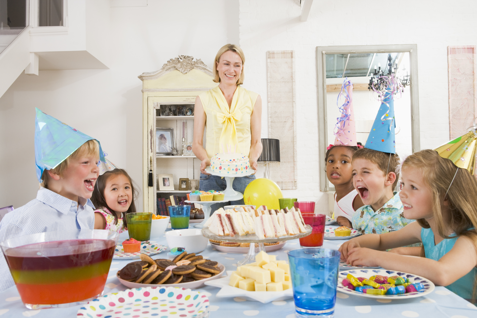 Mom holding kid friendly birthday cake with kids around table celebrating party