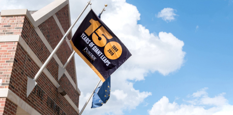 150 Years of Giant Leaps flag hanging from a brick building