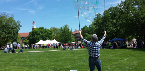 A man making giant bubbles while a crowd of people enjoy Purdue Spring Fling