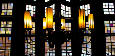 A close-up of a stained glass window and the chandelier handing in front of it