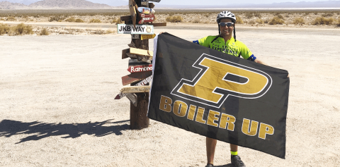 A bicyclist holding a Purdue flag