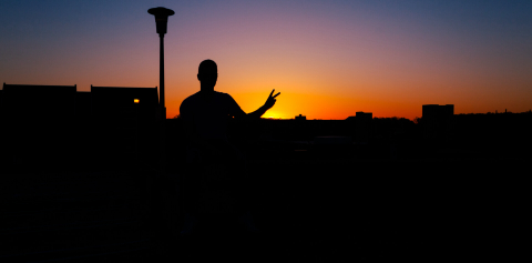 A student in silhouette during sunset