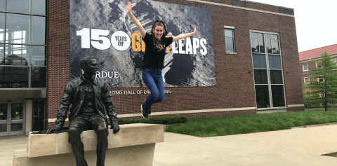 Student jumping in front of Neil Armstrong statue