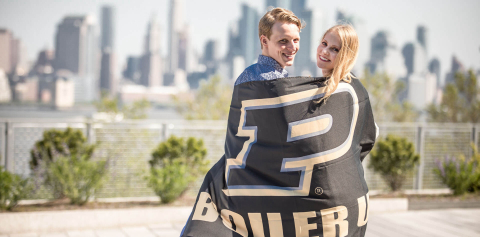 A couple standing in front of the New York City skyline with a Purdue flag