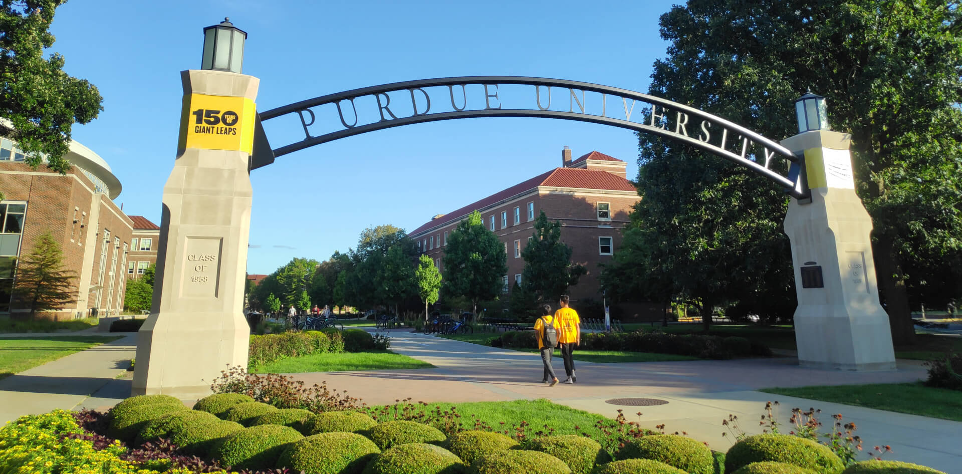 A pair of students walking under the Gateway to the Future Arch