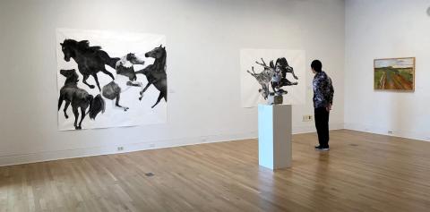 A student contemplating an art piece in a Purdue art gallery
