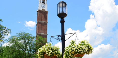 The Purdue Bell tower next to a light post displaying hanging flower baskets
