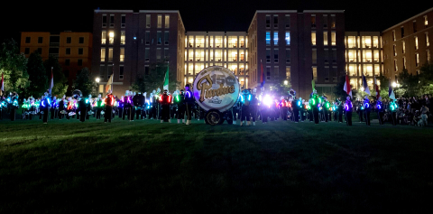The Purdue marching band at night with glowing uniforms