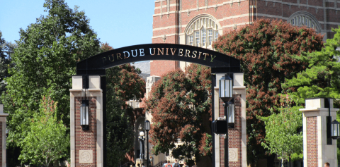 A Purdue arch in front of trees