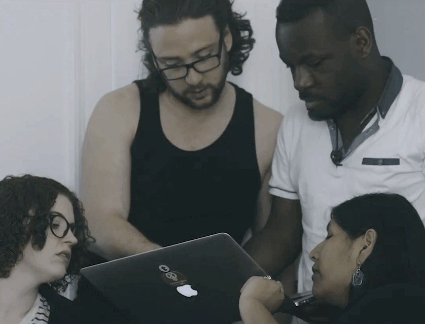 Four developers gathered around a laptop, pair programming together on a piece of work during a ReactJS Academy bootcamp.
