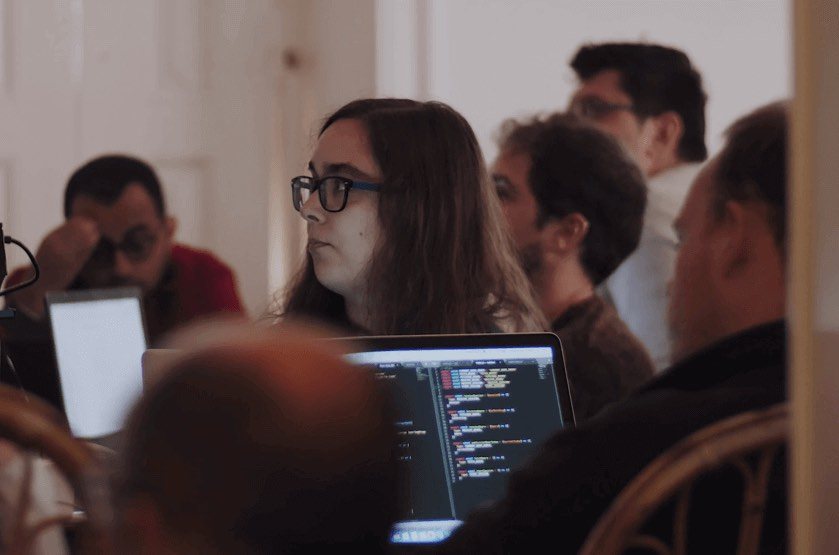 Female ReactJS Academy student wearing glasses concentrating whilst looking into the distance, surrounded by other students with a laptop in the near distance.
