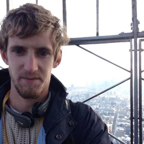 ReactJS Academy coach Adam Lancaster, on top of a tall building as a cityscape is in the background fading out to the horizon