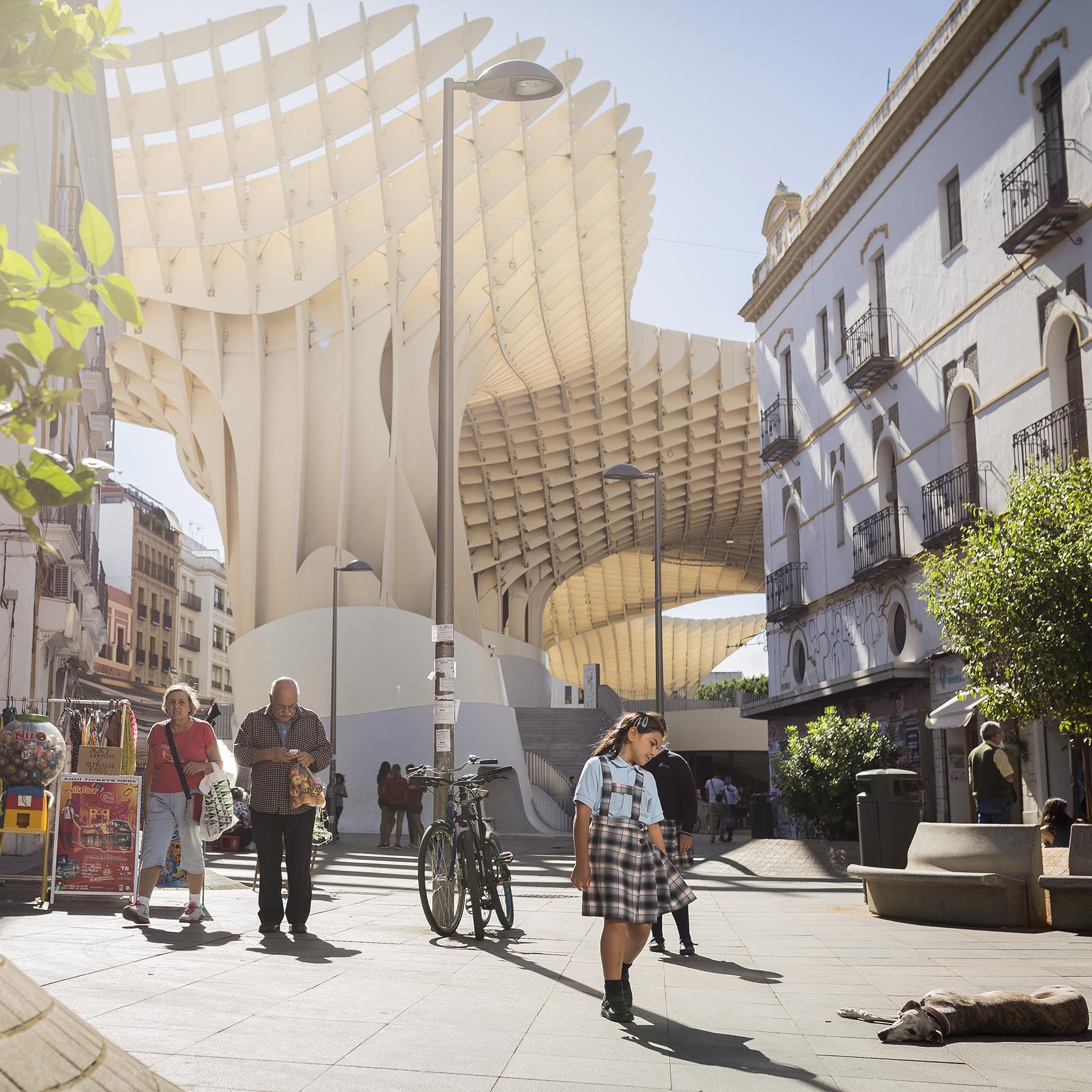A modern architectural structure rises behind traditional buildings and pedestrians in a public plaza.