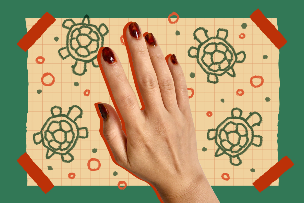 hand with tortoise shell nails on background with turtles