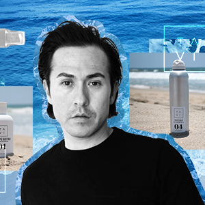 Celebrity hairstylist Octavio Molina on an ocean background surrounded by products from his haircare line Tavi Hair