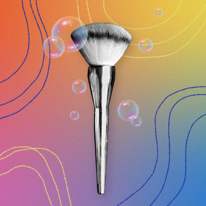 A makeup brush on a rainbow background
