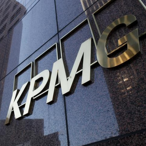 Close up view of KPMG building with company name in gold.