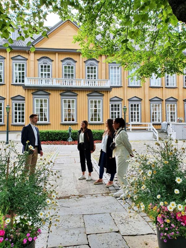 En omviser snakker med en gruppe besøkende. I bakgrunnen ser vi Stiftsgården, i forgrunnen to blomsterkrukker og delvis bladverk fra et stort tre.