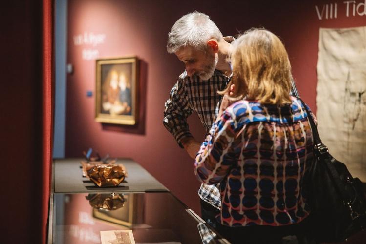 """Kvinne står med ryggen til, vendt mot en mann som ser på et kunstverk i et monter, burgunderfargede vegger i bakgrunnen med kunstverk bl.a maleri i gullramme og utsnitt av en tekst """"VIII Tid"""""""