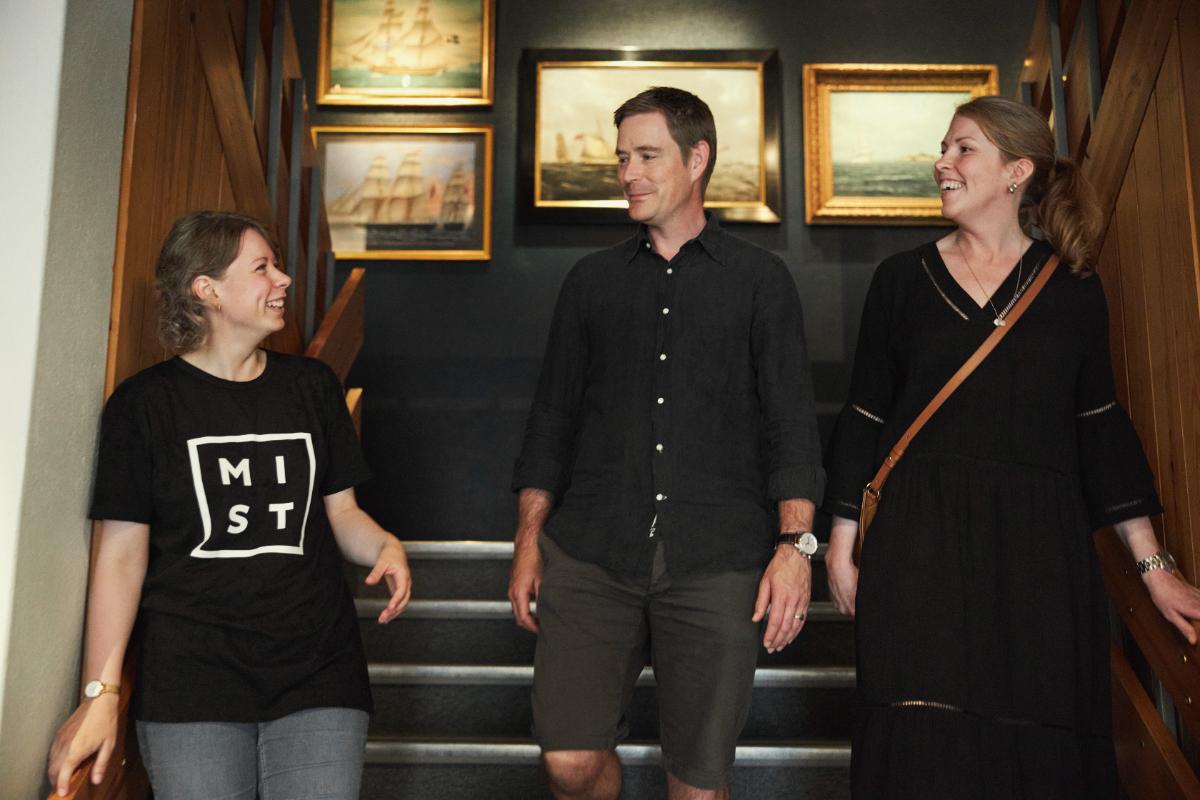 To voksne får omvisning av en MIST ansatt. Seilskuteportrett i bakgrunnen.