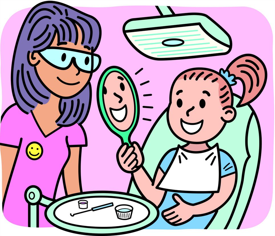A girl looking at her cleaned teeth in a mirror at the dentist's office.