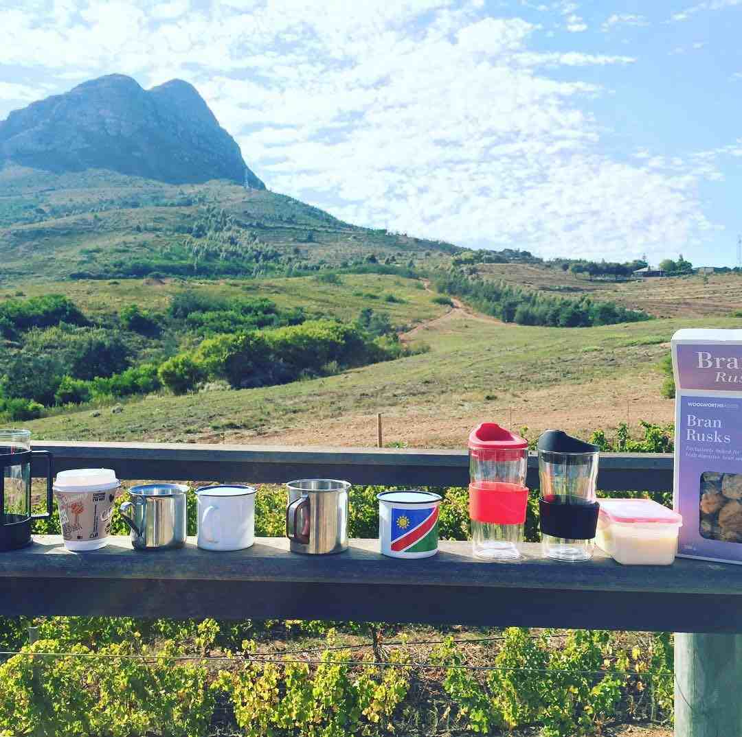 Image of a lush, green mountain background with a ledge in the foreground with mugs, bottles, and flasks. There is also a box of rusks.