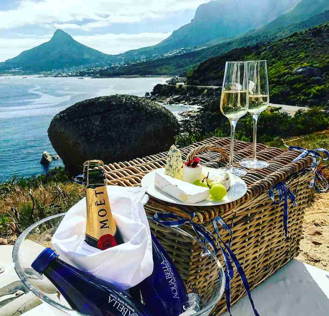 Image of a picnic basket with  cheese platter, sparkling wine, and two glasses. this overlooks the ocean Head and Lion's Head