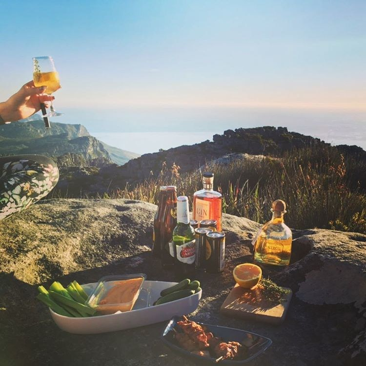 Image of a picnic on top f some rocks at the top of Table Mountain. There is chicken, vegetables, dip, and an array of drinks. A hand holds a full glass. In the background there is ocean and more mountain
