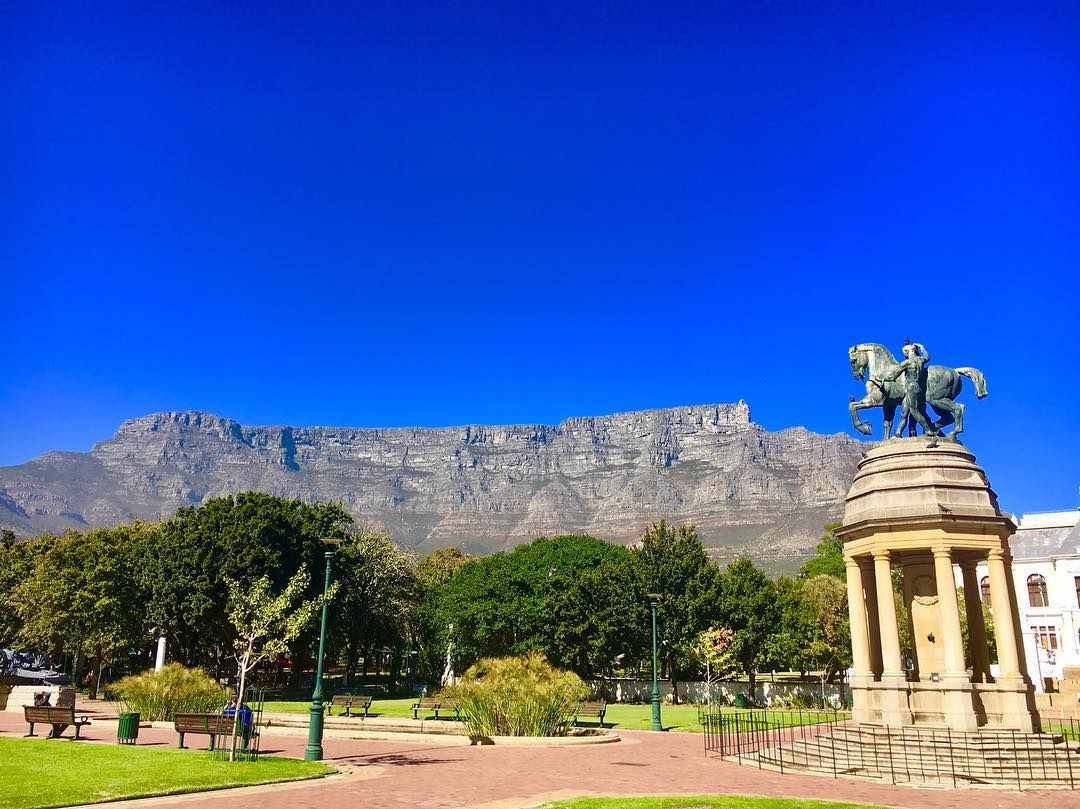 Green lawns separated by a pathway with a statue of a man and a horse in the middle. I the backgrounds there are trees and Table Mountain