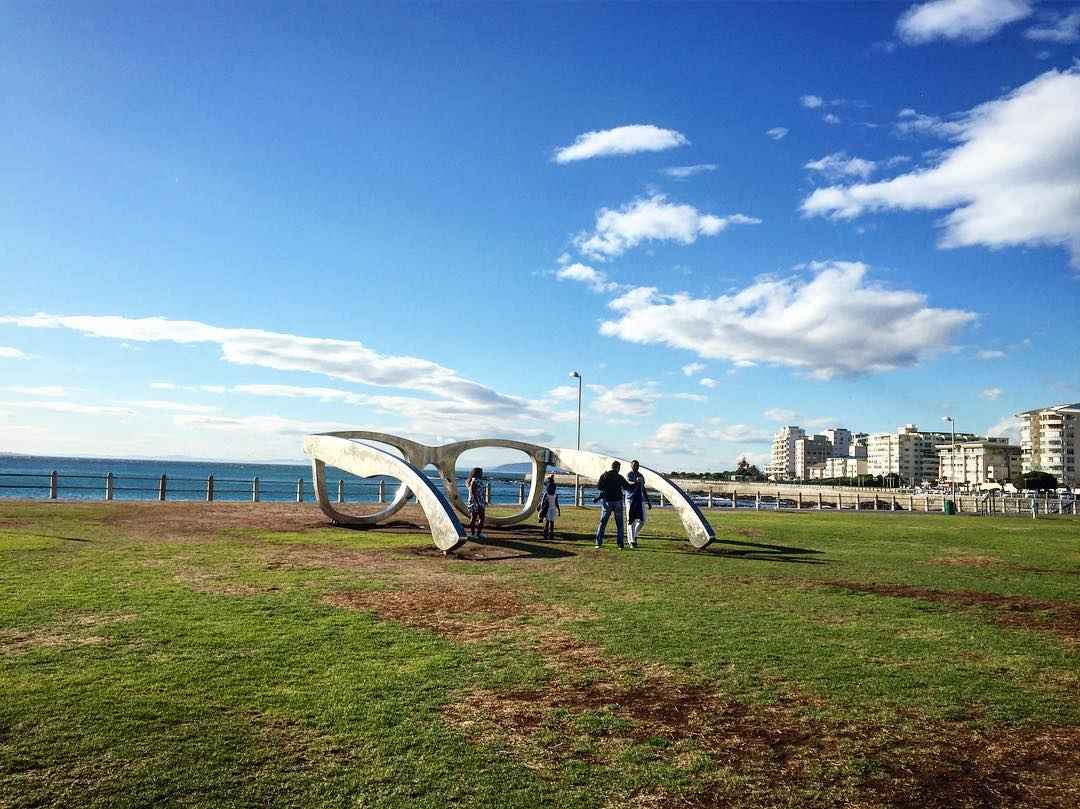 Large lawn with a sculpture of giant sunglasses. In the background there is ocean and sky.