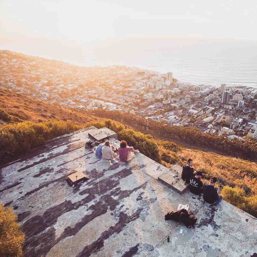 A group of people sitting atop Signal Hill with picnics overlooking the ocean and the Atlantic Seaboard