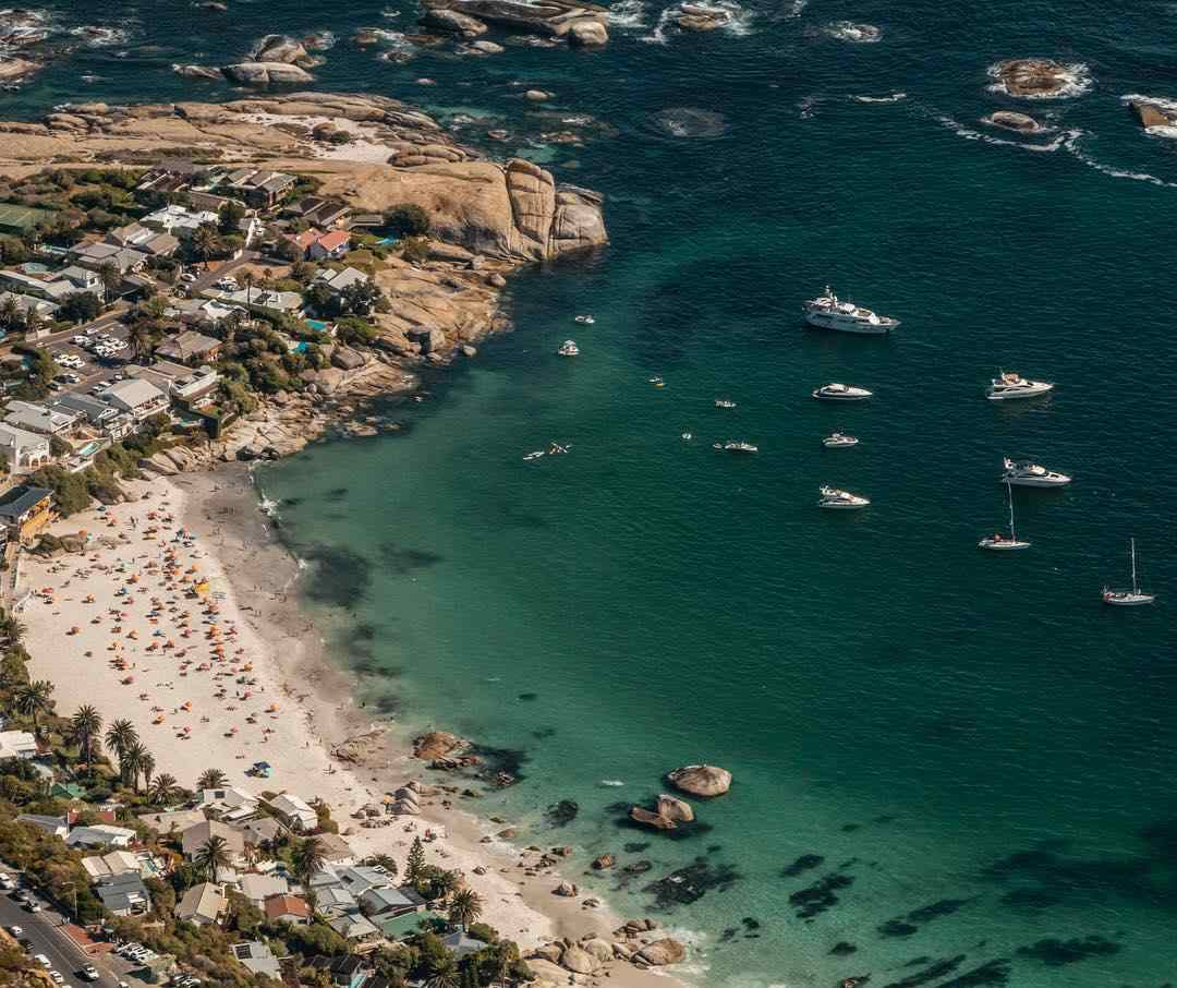 aerial shot of Clifton beach with yachts and boats  in the water and sunbathers on the beach.