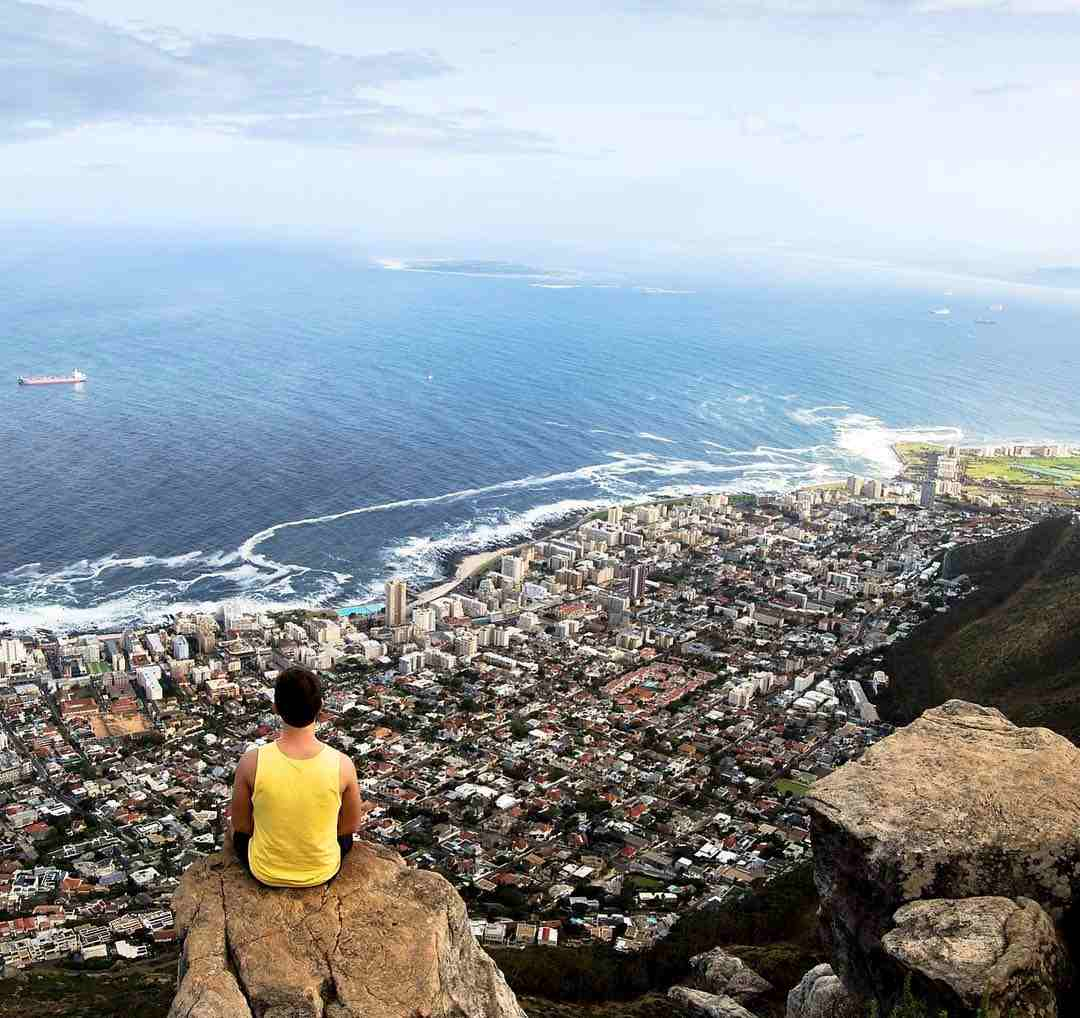 Image of a man sitting on the edge of Lion's Head. His back is to us. The view ahead is of the ocean and the city