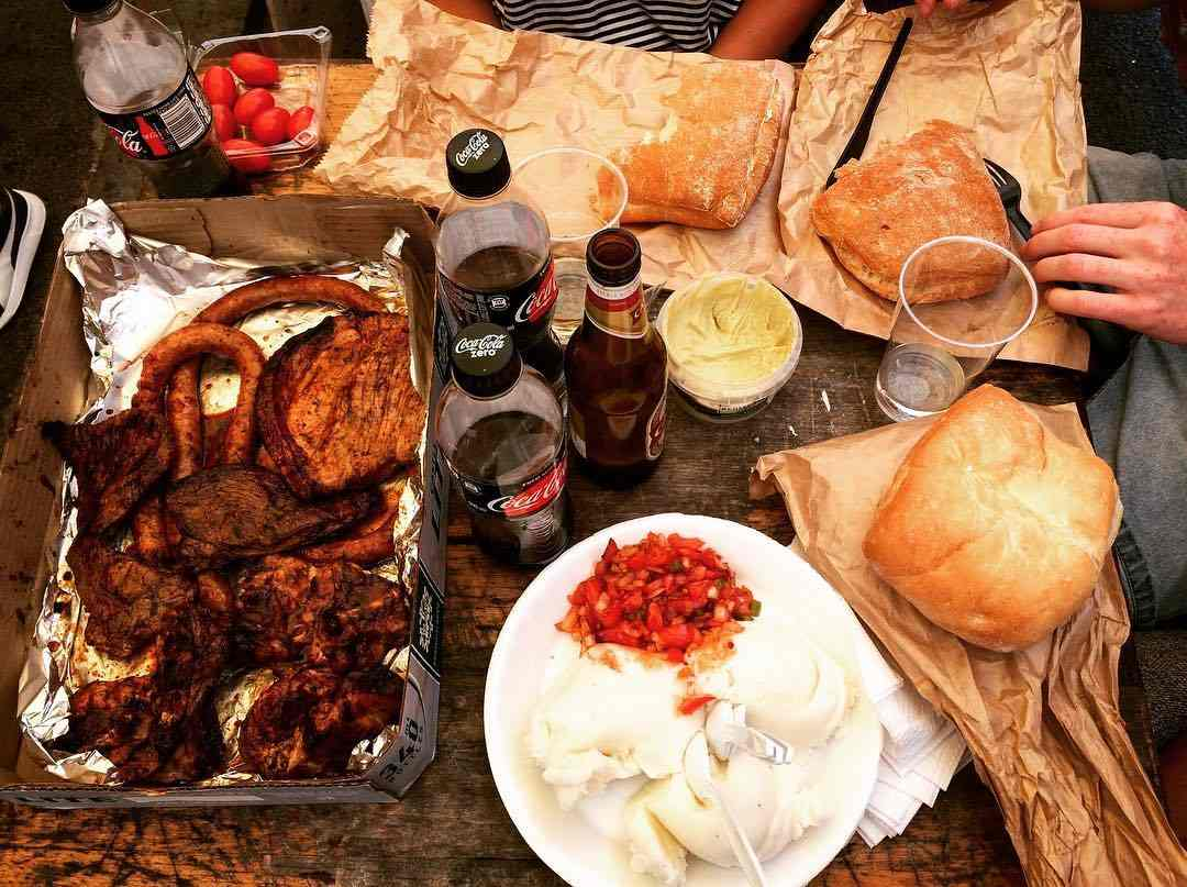Close up of a table with a box of barbequed meat, bread, drinks, and pap