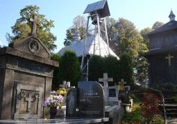 Cmentarz przycerkiewny z dzwonnicą w tle